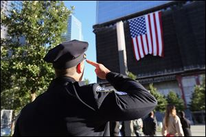 A New York City Police officer salutes a flag hanging from the One World Trade Center building, during ceremonies for the 11th anniversary of the attacks at the World Trade Center, in New York.