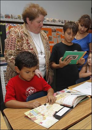 Sister Frances Marie watches Augustine Vallejo, 7, and his brother Armando Vellejo, right, as they choose free books.