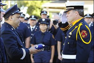 Fire Station 6 Captain Dave Rodriguez, left, accepts the station flag from Private Jeff Koenigseker, commander of the Toledo Fire Department Honor Guard, during a 9/11 Commemoration Ceremony and Dedication of Fire Station 6 at 1155 Oak Street, Tuesday.