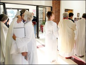 Beverly Bingle, left, gets a hug from Rev. Elsie McGrath of St. Louis before her ordination as a deacon at the First Unitarian Church.