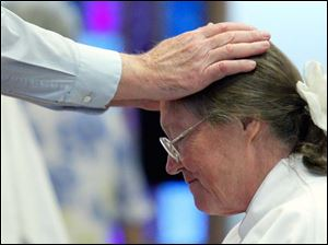 A member of the congregation lays hands on Beverly Bingle during her ordination at the First Unitarian Church.