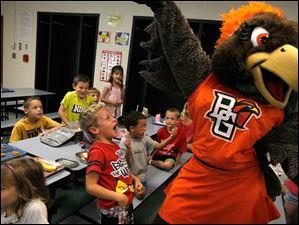 Alexander Diaz, 6, screams while Frieda Falcon leads his fellow first graders in a cheer during. Frieda is one of two mascots for the Bowling Green State University Falcons.