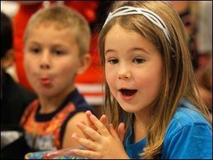Catherine Kerber, 5, claps while listening to cheerleaders lead her fellow kindergartners in a cheering competition during led by Toledo and Bowling Green cheerleaders.