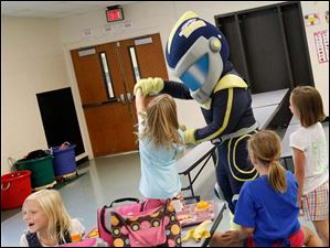 University of Toledo mascot Rocky dances with a student during a lunchtime visit.