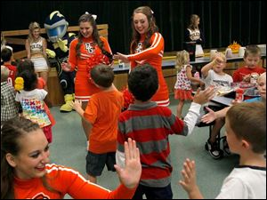 Cheerleaders from both the University of Toledo and Bowling Green State University, including Megan Gill, left, Carissa Mills, center, and Tori Allen, right, give high-fives to children on their way out to recess from lunch.