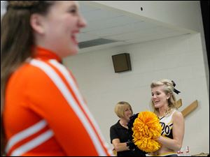 Bowling Green cheerleader Carissa Mills, left, shared cheering space in the cafeteria with University of Toledo cheerleader Ashley Arndt, right. The schools are rivals and face each other Saturday night.
