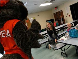 Carly Williamson, 6, leaps out of her seat to greet Frieda the Falcon during a visit to Fort Meigs Elementary.