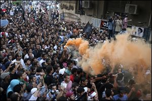 Protesters chant slogans amid orange smoke outside the U.S. embassy in Cairo, Egypt.