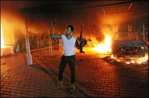 An armed man waves his rifle as buildings and cars are engulfed in flames after being set on fire inside the U.S. consulate compound in Benghazi.