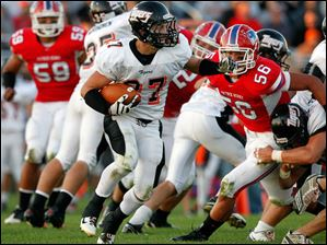 Liberty Center running back Anthony Righi runs the ball as he eludes Patrick Henry defender Caleb Carrizels (56).