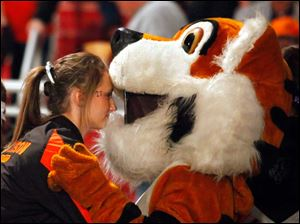 Liberty Center cheerleader Allison Righi hugs Monica Mann, who is dressed as the team's Tiger mascot.