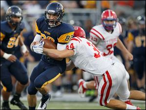 St. Francis De Sales High School player John Fudacz, 34, tackles Whitmer High School player Michael Dzikowski, 82, during the second quarter at Whitmer High School.