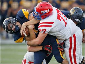 St. Francis De Sales High School player Sam Burns, 77, tackles Whitmer High School quarterback Nick Holley, 7, during the first quarter at Whitmer High School.