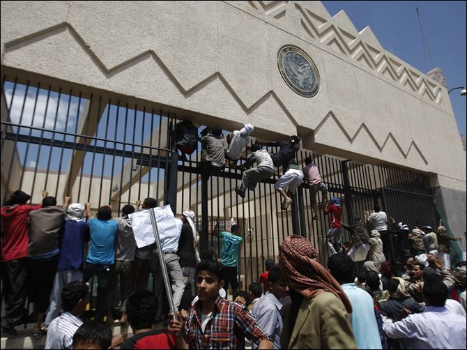 APTOPIX Mideast Yemen Protesters scale the main gate outside the U.S. Embassy in Sanaa, Yemen, on Thursday in anger over the release of a U.S.-made video critical of the prophet Mohammed, depicting him as being of questionable moral character.