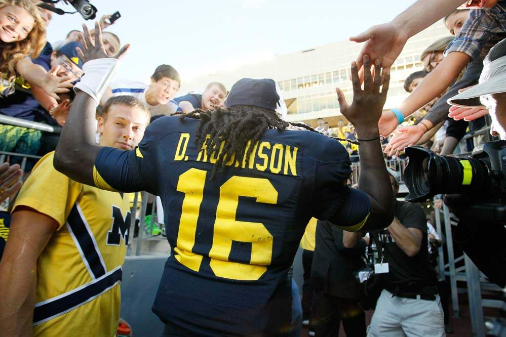 University-of-Michigan-fans-high-five-quarterback