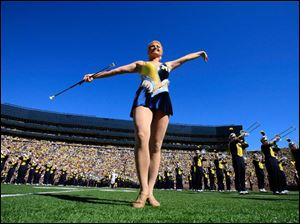A University of Michigan baton twirler performs before the Wolverines take the field against the University of Massachusetts at Michigan Stadium in Ann Arbor.