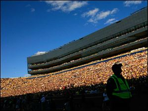A Washtenaw County Sheriff's Deputy keeps an eye on another sell out crowd as the University of Michigan plays the University of Massachusetts at Michigan Stadium in Ann Arbor.