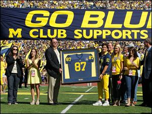 Family members of former University of Michigan great Ron Kramer pose with his Legends jersey and Athletic Director David Brando, right,  during a pre-game presentation before the Wolverines play the University of Massachusetts at Michigan Stadium in Ann Arbor.