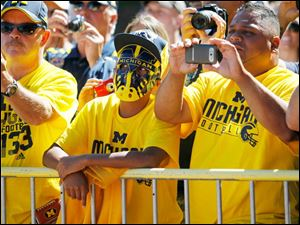 Tyreese Fontanez, 13, in mask, and his father Ray Fontanez, right, Grand Rapids, Michigan, watch as the University of Michigan Wolverines arrive at Michigan Stadium to play the University of Massachusetts in Ann Arbor.