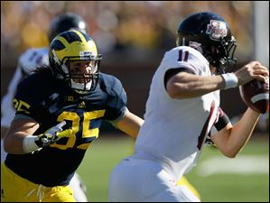 University of Michigan defender Joe Bolden, 35, chases University of Massachusetts quarterback Mike Wegzyn, 11, causing him to throw the ball and get flagged for intentional grounding during the second quarter at Michigan Stadium in Ann Arbor.