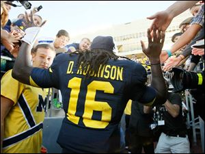 University of Michigan fans high-five quarterback Denard Robinson after the Wolverines defeated the University of Massachusetts at Michigan Stadium in Ann Arbor.