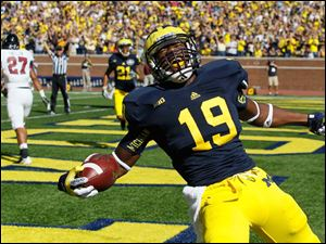 University of Michigan player Devin Funchess, 19, celebrates his first quarter touchdown against the University of Massachusetts at Michigan Stadium in Ann Arbor.