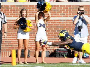 University of Michigan player Devin Gardner, 12, dives into the end zone for a touchdown during the second quarter against the University of Massachusetts at Michigan Stadium in Ann Arbor.