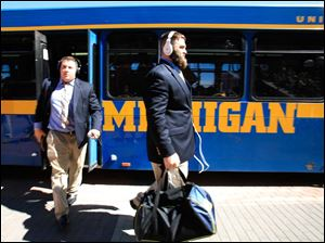 University of Michigan player Elliott Mealer, right, leads the team off of the bus and into Michigan Stadium as the Wolverines arrive to play the University of Massachusetts in Ann Arbor.