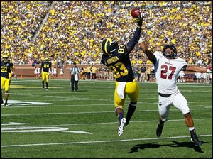 University of Michigan player Jerald Robinson, 83, almost makes a great catch as University of Massachusetts player Darren Thellen, 27, defends during the first quarter at Michigan Stadium in Ann Arbor.