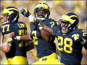 University of Michigan players Vincent Smith, 2, and Fitzgerald Toussaint, 28, celebrate Toussaint's touchdown during the first quarter against the University of Massachusetts at Michigan Stadium in Ann Arbor.