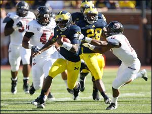 University of Michigan quarterback Denard Robinson, 16, streaks past Randall Jette, 17, and the rest of the University of Massachusetts defense during the second quarter at Michigan Stadium in Ann Arbor.