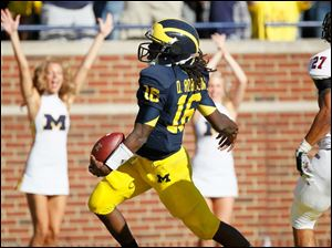 University of Michigan quarterback Denard Robinson, 16, sprints past University of Massachusetts defender Darren Thellen, 27, for a touchdown in the second quarter at Michigan Stadium in Ann Arbor.