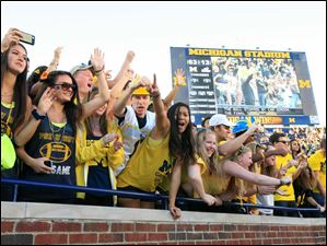 University of Michigan students celebrate the Wolverine's 63-13 win over the University of Massachusetts at Michigan Stadium in Ann Arbor.