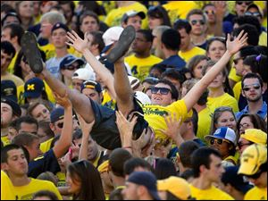 University of Michigan students celebrate another Wolverine touchdown during the second quarter against the University of Massachusetts at Michigan Stadium in Ann Arbor.