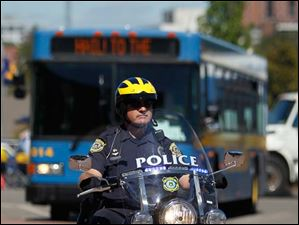 A police officer escorts the University of Michigan University bus to Michigan Stadium in Ann Arbor.