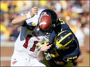 University of Michigan player Frank Clark, 57, hits University of Massachusetts quarterback Mike Wegzyn, 11, during the first quarter at Michigan Stadium in Ann Arbor.