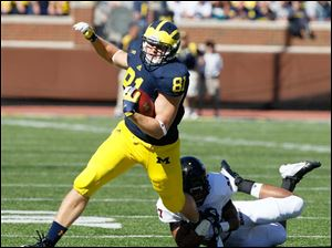 University of Michigan player Mike Kwiatkowski, 81, picks up a first down on a pass reception before being brought down by University of Massachusetts player Darren Thellen, 27, during the first quarter at Michigan Stadium in Ann Arbor.