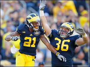 University of Michigan players Roy Roundtree, 21, and Joe Kerridge, 36, celebrate Roundtree's third quarter touchdown against the University of Massachusetts at Michigan Stadium in Ann Arbor.