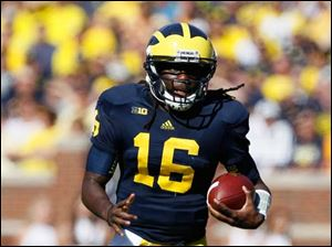 University of Michigan quarterback Denard Robinson takes off on a long run despite losing a shoe during the first quarter against the University of Massachusetts at Michigan Stadium in Ann Arbor.