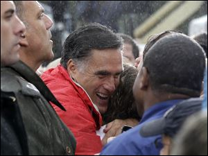 Republican presidential candidate Mitt Romney hugs a supporter as he campaigns in the rain.