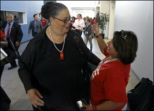 "Karen Lewis, president of the Chicago teachers union, left, is greeted by a union member after her meeting with the union's House of Delegates. Lewis told the delegates that a ""framework"" was in place to end the teachers strike."