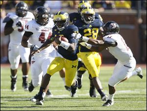Michigan's Denard Robinson streaks past Randall Jette and the rest of the University of Massachusetts defense. Robinson racked up 397 yards for the Wolverines.