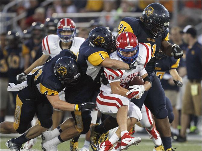 St. Francis De Sales High School player Michael Wagner is swarmed by Whitmer High School defenders Jack Linch, 44, Devin Thomas and Marquise Moore, 91, during the second quarter Friday at Whitmer High School.