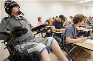 Kyle Cannon,18, listens in class while his health aid, Dan Dorner, center in baseball cap, takes notes for him at Bowling Green State University. Canon was a Clay freshman when he was paralyzed during a hockey game in 2008.
