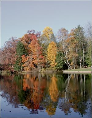 Brilliant fall leaves are reflected on the waters of Mallard Lake at Oak Openings Preserve Metropark.