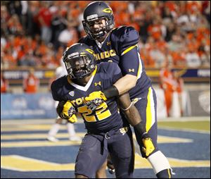 Toledo running back David Fluellen, 22, celebrates with teammate Zac Rosenbauer after scorin