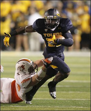 Toledo running back David Fluellan carries the ball as Bowling Green defensive lineman Ted Ouellet holds on during the fourth quarter.