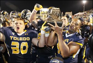 University of Toledo players including Ben Pike, 30, and Danny Farr, 92, holding Battle of I-75 trophy. Toledo celebrated after beating Bowling Green 27-15 at the Glass Bowl.