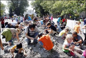 Children and parents swarm the mound of rocks looking for fossils during Fossil Fest on Sunday  at Sylvania Historical Village.
