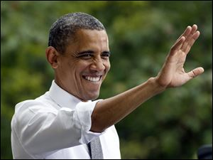 President Barack Obama waves to the crowd at a campaign event at Eden Park's Seasongood Pavilion, Monday in Cincinnati.